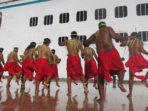 Dancers greet the arriving visitors on tarmac still wet from the rain